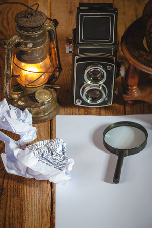 Vintage still life stuff on a rustic wooden table,retro camera, glasses, pencil, pen, old rusty kerosene lamp. photo