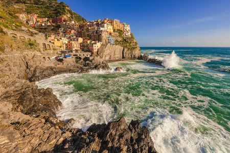 Rock coast of the Cinque Terre National Park, colorful town of Manarola, Italy photo