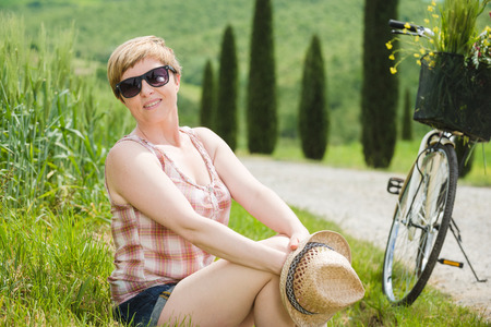 green fields: Young beautiful blond woman on vacation in Tuscany, riding a bicycle between cypresses.