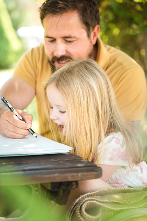 homework: Father with daughter in the garden at the table, doing homework in a summer day. Stock Photo