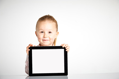 Cute little and smiling girl plays with a tablet Фото со стока - 42810533