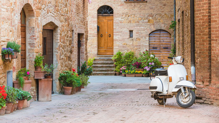 Italian streets in the Tuscan small town and a popular single-track vehicle, an old scooter 스톡 콘텐츠