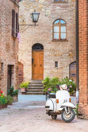 Italiaanse straten in het Toscaanse stadje en een populaire single-track auto, een oude scooter