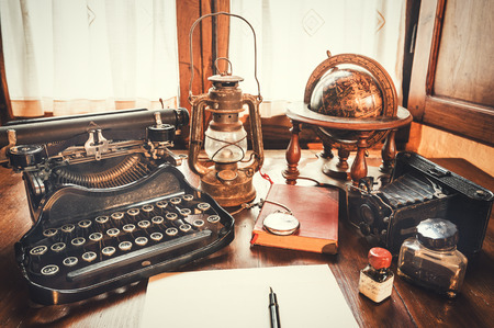 old page: Vintage items, camera, pen, globe, clock, typewriter on the old desk