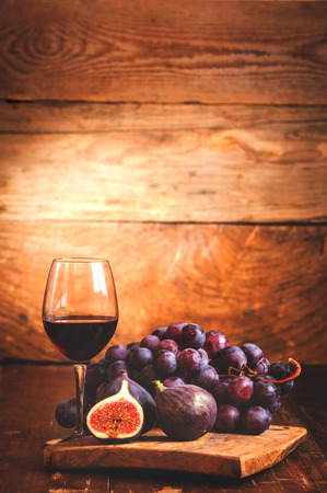 italian landscape: Fig with red wine, grape and barrel on rustic wood tabel