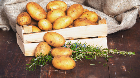unboiled: Potatoes in a box on a rustic wooden table Stock Photo