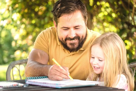 deberes: Padre con la hija en el jardín en la mesa, hacer la tarea en un día de verano.