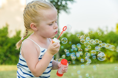 Jouer Sympathiquement fille et son des bulles de savon Banque d'images - 43082498