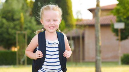 Schoolgirl Returning to school after the holidays, smiling and cheerful, with a rucksack