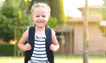 colegiala: Colegiala De regreso a la escuela después de las vacaciones, sonriente y alegre, con una mochila Foto de archivo
