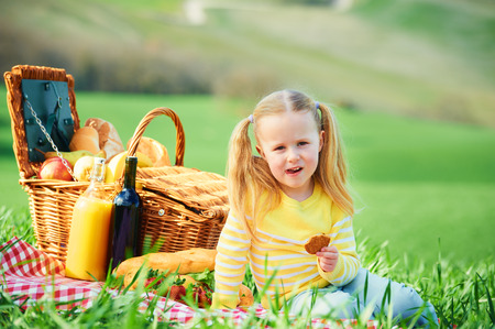 spring landscape: Beautiful smiling girl on green spring grass in the background landscape of Tuscany. Stock Photo