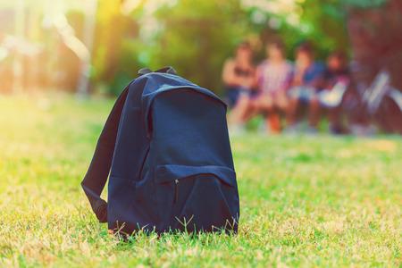convivencia escolar: Mochila azul de la escuela de pie sobre la hierba verde con estudiantes en el fondo Foto de archivo