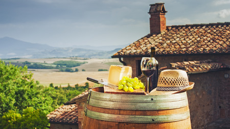 Red wine, cheese, grapes and a straw hat on a wooden barrel on the background of the Tuscan landscape, Italy Фото со стока