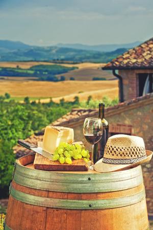 Rode wijn, kaas, druiven en een strooien hoed op een houten vat op de achtergrond van het Toscaanse landschap, Italië
