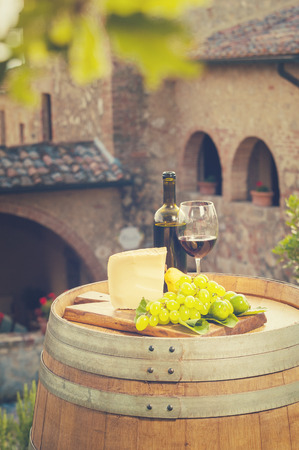 italian landscape: Red wine, pecorino cheese, grapes, bottle and glass on wooden barrel in the background of the Tuscan landscape, Italy Stock Photo