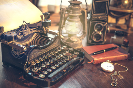 vintage photography still life with typewriter, folding camera, globe map and book on a wood table. Фото со стока - 44027834