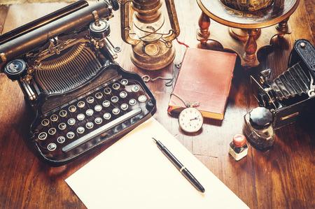 Itens vintage, câmera, caneta, globo, relógio, máquina de escrever na mesa velha