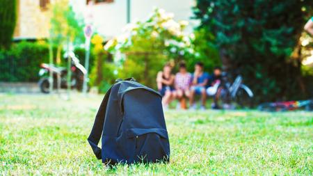 Blauwe schoolrugzak die zich op groen gras met studenten op achtergrond bevindt