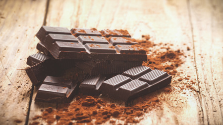 eating chocolate: Noble dark chocolate on a wooden table in vintage style.