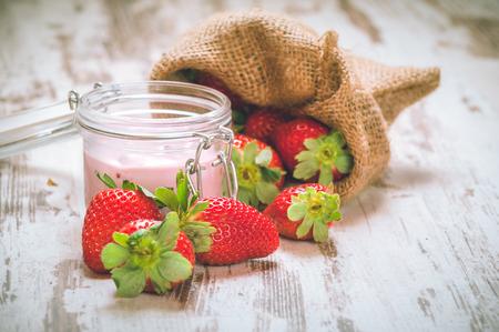 stole: Owoce Wiosenne, truskawki w lnianym worku z truskawkowym jogurtem na drewnianym vendimia robó.