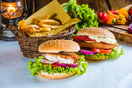 burger: Juicy and tasty looking fish burger with fried potatoes