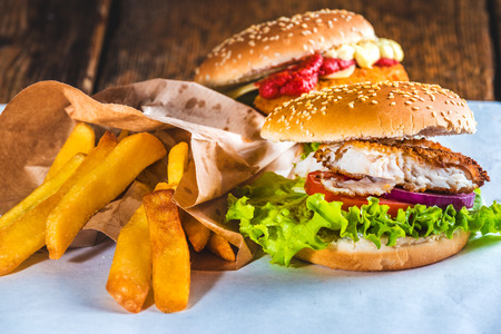 Fish burger with rustic chips on white paper for takeaway Фото со стока