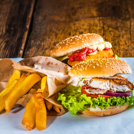delicious food: Fish burger with rustic chips on white paper for takeaway Stock Photo