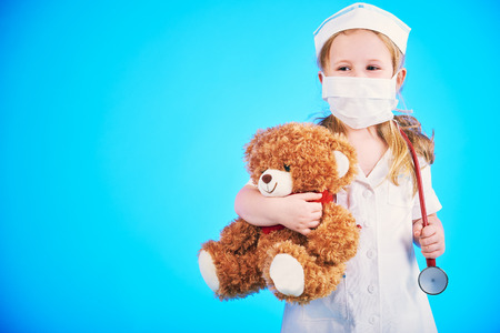 cute teddy bear: Beautiful doctor, nurse examines teddy bear on a blue background