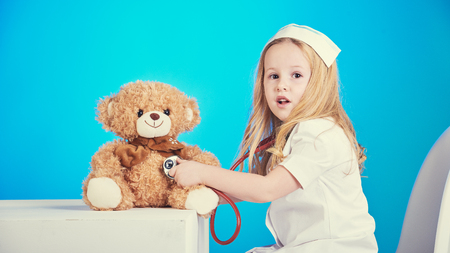 sick teddy bear: Beautiful nurse examiner little sick brown teddy bear.