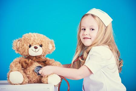 bebe enfermo: Hermosa enfermera examinador poco enfermo oso de peluche marr�n. Foto de archivo