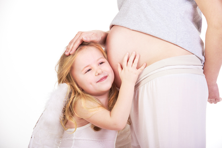vientre femenino: La hermosa rubia modelo de cabello de ángel abrazos vientre de embarazada.