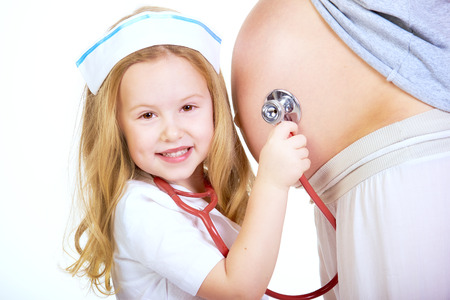 minors: Minors blond hair doctor examines a pregnant belly. Stock Photo