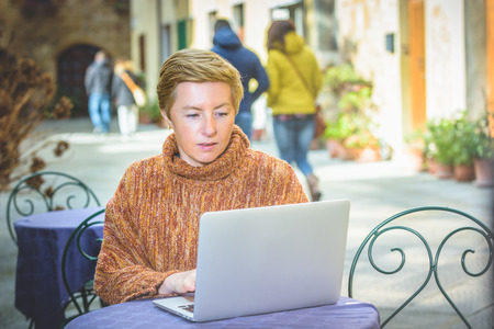 tabel: Young blond woman freelancer working outside on tabel Stock Photo