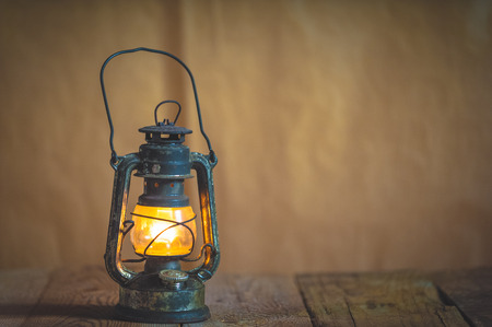 antique table: vintage kerosene oil lantern lamp burning with a soft glow light in an antique rustic country barn with aged wood floor