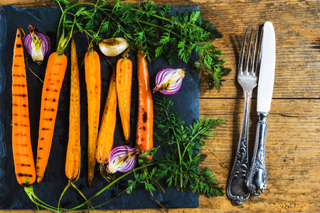vintage cutlery: Grilled juicy carrots with parsley and vintage cutlery Stock Photo