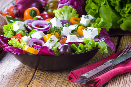 Crisp spring salad with feta cheese, full of vitamins and colors. Greec Salad on vintage table Фото со стока