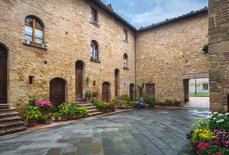 Flowery streets on a rainy spring day in a small magical village Pienza, Tuscany. Stock Photo