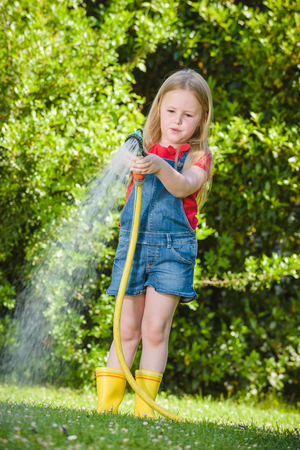 hosepipe: Beautiful blond girl watering flowers, lawn on a sunny beautiful day in front of the house. Stock Photo
