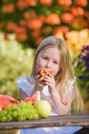Fruity smile girl eating a vitamin in the form of nectarines. Stock Photo
