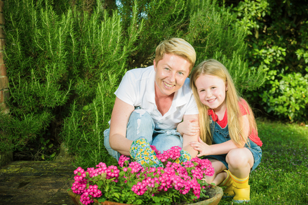 family gardening: Family gardening all. Daughter with her mother in the garden replant flowers.