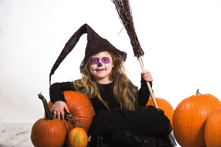 Terribly serious and dangerous witch, a girl dressed  for halloween holiday and the pumpkins.