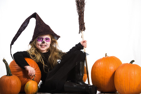 terribly: Terribly serious and dangerous witch, a girl dressed  for halloween holiday and the pumpkins.