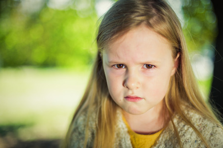 Angry at her parents a little girl sitting on a park bench.