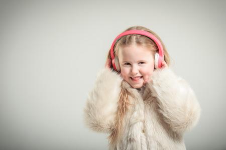 pink fur: Party girl in pink fur coat and headphones. Stock Photo