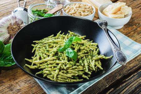 Trofiedeeg met vegetarische saus, pesto met pijnboompitten en basyli. Stockfoto