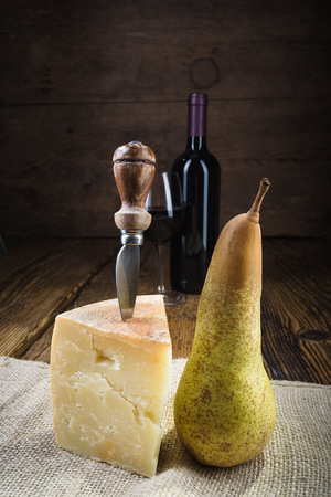 Red wine in vintage light with cheese and fruits. Stock Photo