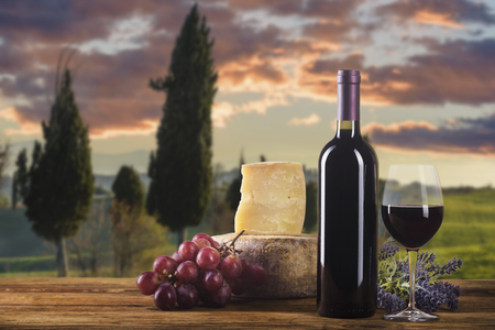 bottle opener: Red wine in vintage light with cheese and fruits. Stock Photo