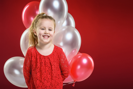 Party balloons in red, blond girl plays with.