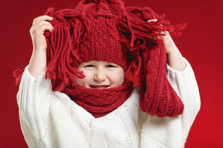 Beautiful blond girl playing in the winter warm hat and scarf on red background Фото со стока