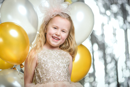 Little beautiful girl at a party with balloons.